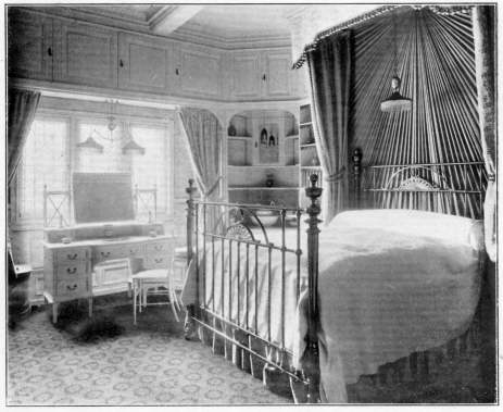 Edwardian bedroom  with iron bedstead and spectacular curtaining